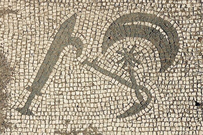 A mosaic with a sword, a moon crescent, Hesperos/Phosphoros, and a pruning knife that was found within a second-century Mithraeum.