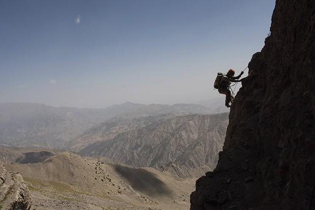 A climber on a rope descending a rock face © Robbie Shone